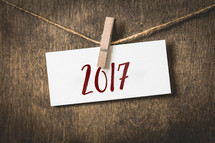 year 2017 on white card stock hanging from a clothespin on a clothesline