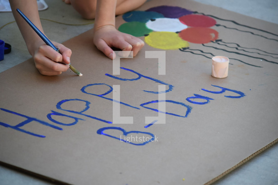 A child painting a Happy Birthday sign