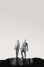 silhouettes of a couple holding hands with branches