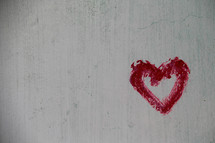 Red painted heart on textured wall background