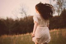 teen girl walking through a field