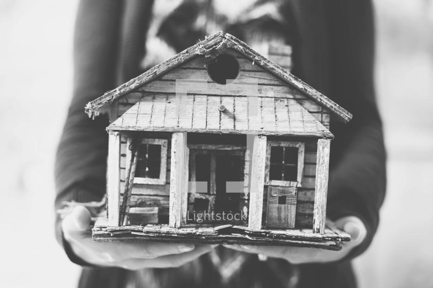 woman holding a birdhouse