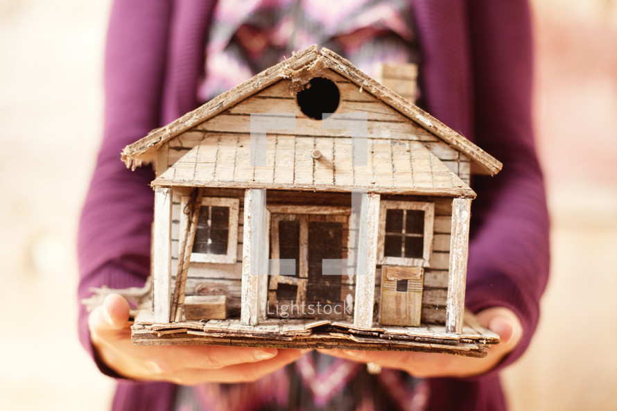 Woman holding a homemade bird house.