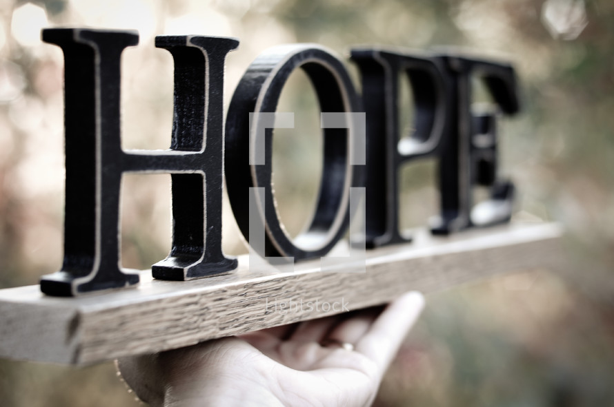 "Hand holding a board with letters spelling ""hope."""