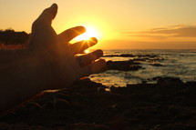 reaching hand at sunrise and the ocean
