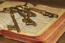 Large bunch of keys on the pages of an old Bible