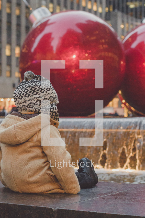 toddler boy in winter coat and hat and Christmas decorations