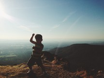little boy at the top of a mountain - karate pose
