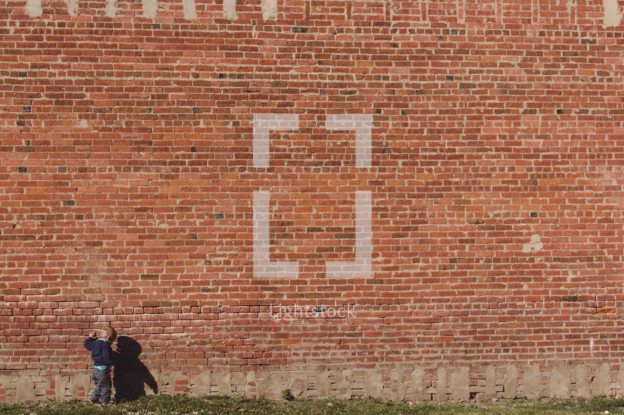 toddler boy in front of a brick wall