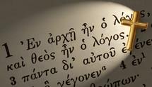 Gold cross on Greek Bible text.