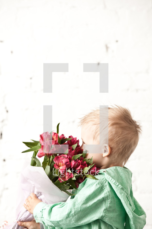 Boy smelling a bouquet of flowers.