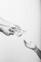 Hands giving money to an empty hand.