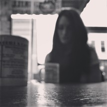blurry image of a woman sitting in a coffee shop