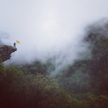 man holding a yellow flag a the edge of a steep drop off in the mountains