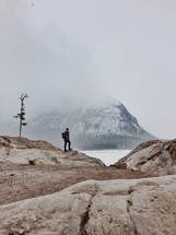 Man standing on a rock looking at a snow-covered mountain.
