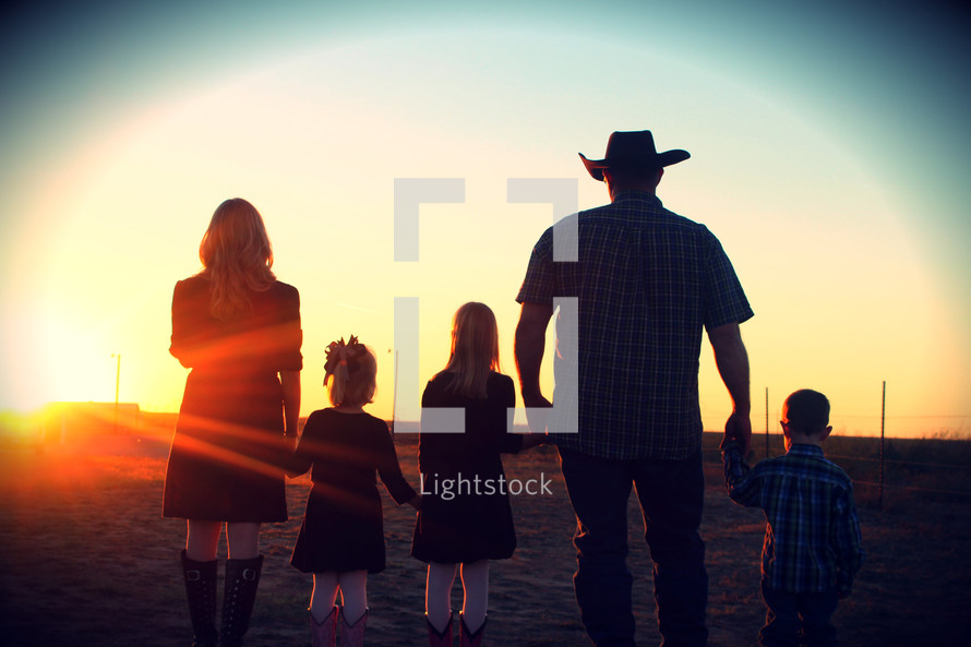 Family in westernwear standing in field at sunset.