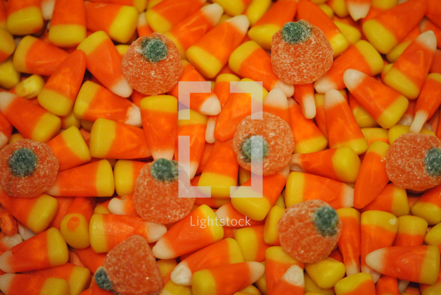 Candy corn and gumdrop pumpkins for Halloween or Thanksgiving; closeup, texture.