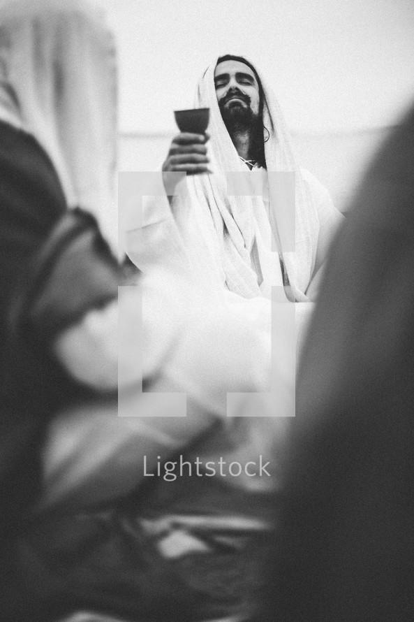 Jesus raising wine in blessing at communion