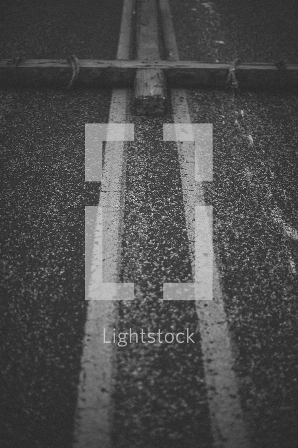 large cross lying on the center lines of a highway
