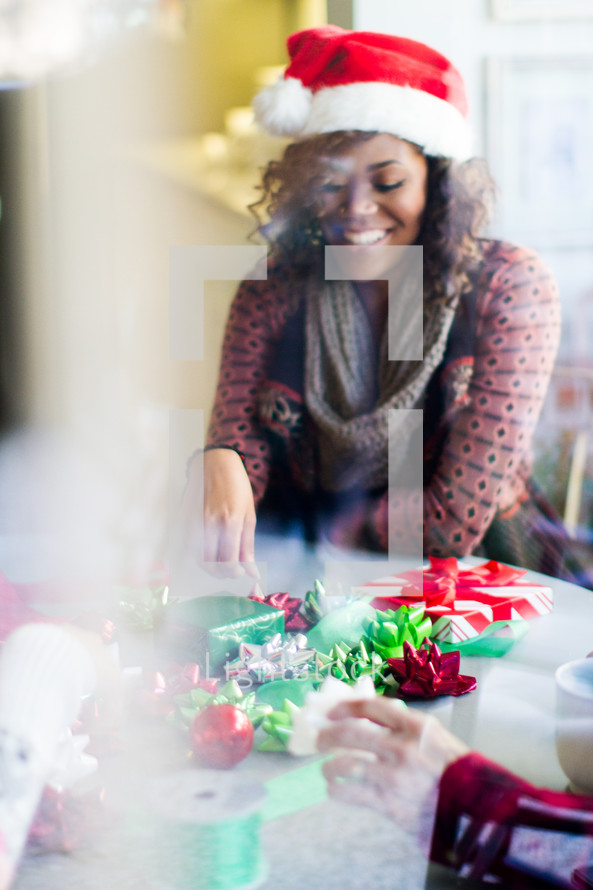 A woman in a santa hat wrapping presents