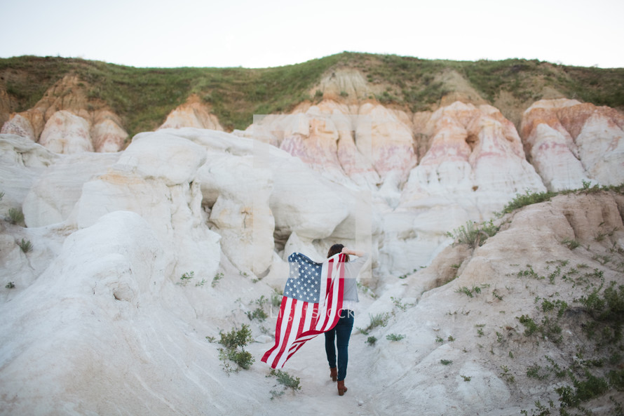a woman walking carrying an American flag on her back