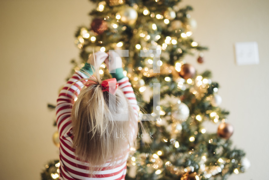 toddler girl decorating a Christmas tree
