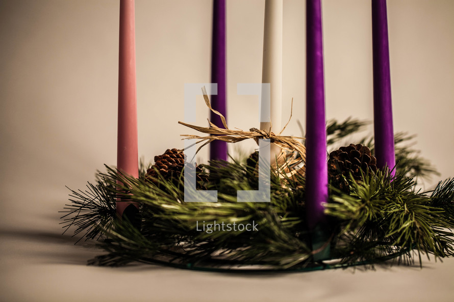 Five candles in pine wreath with pine cones.