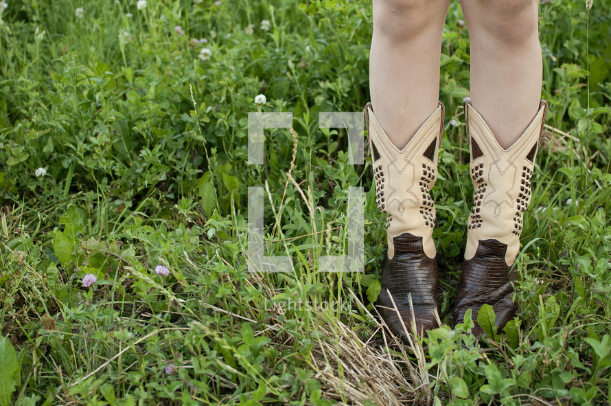 child in cowboy boots in grass