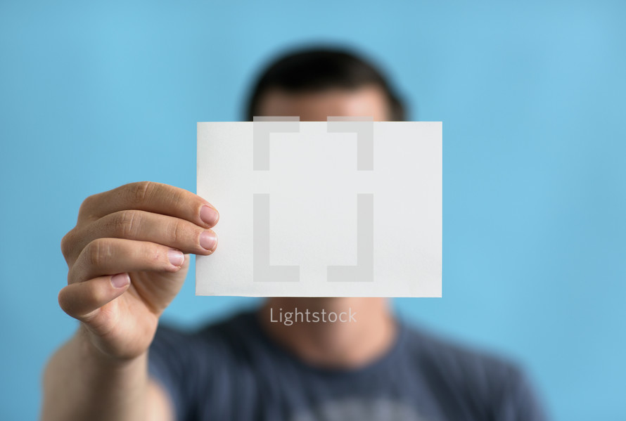 a man holding up a blank piece of paper