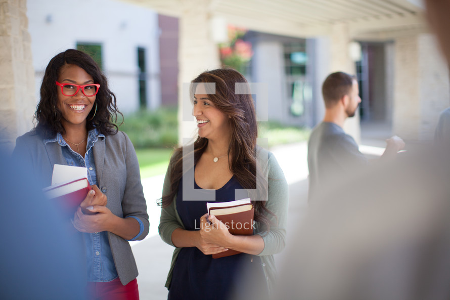 young women in conversation holding Bibles