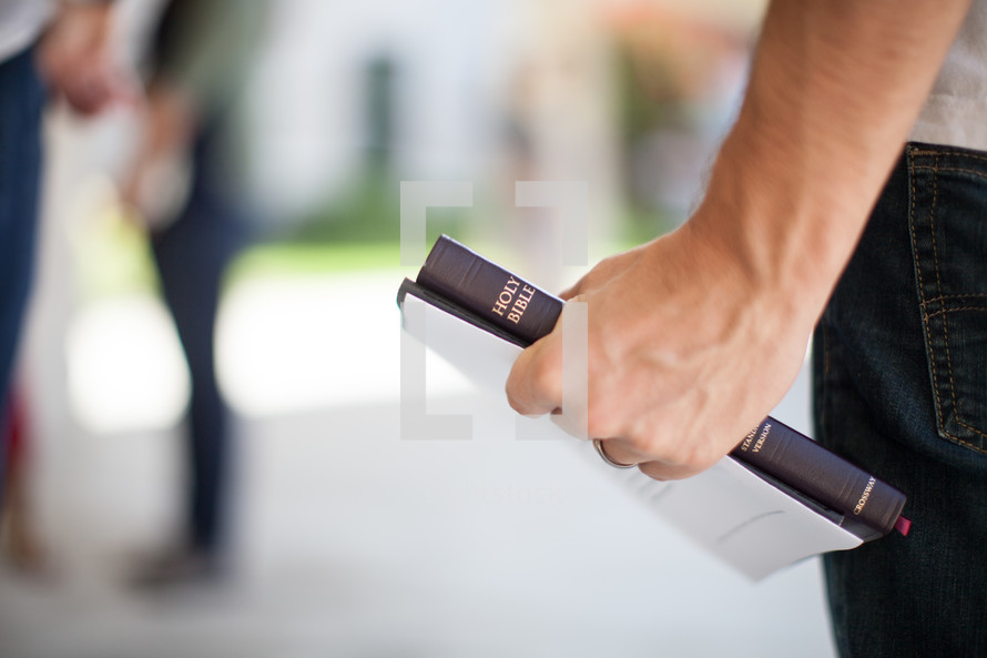 man holding a bulletin and Bible in his hand