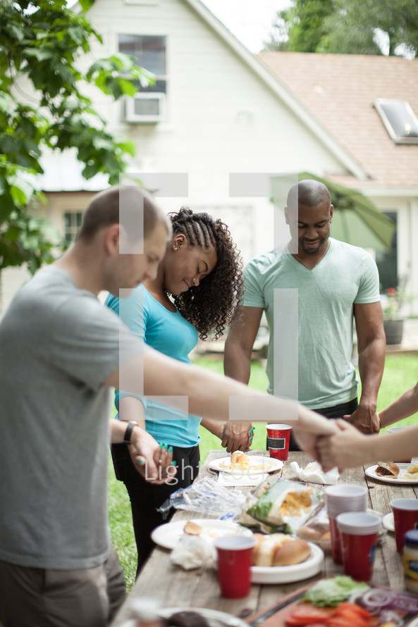 holding hands in prayer over an outdoor table before a meal
