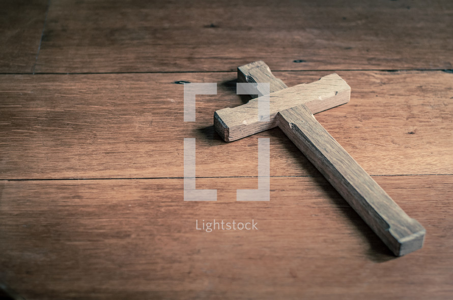 Wooden cross on a wooden table.