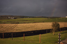 farmland under a gray sky with rainbow