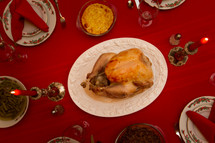 turkey on a platter in the center of a set table