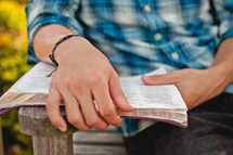 a man sitting on a bench reading a Bible