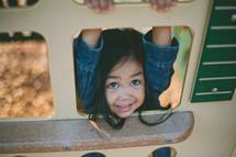 A little girl climbing on playground equipment.