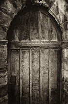 Arched wooden doorway in an ancient stone cathedral.