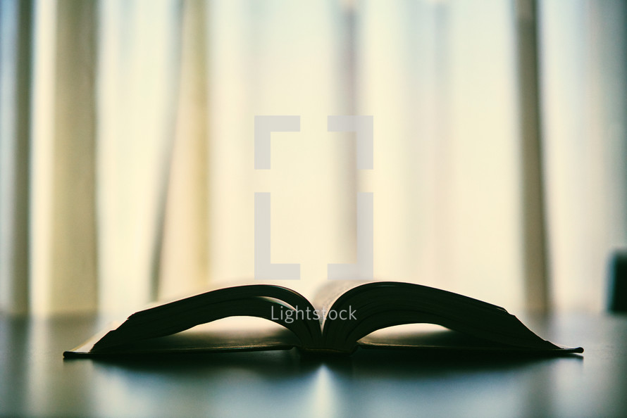 Silhouette of open Bible sitting on table