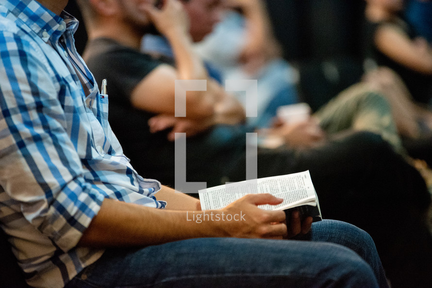 men sitting with Bibles in their lap