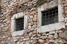 Hand made antique prison bars in stone walls.