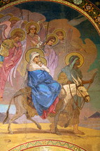 Joseph and Mary and baby Jesus riding on a donkey
