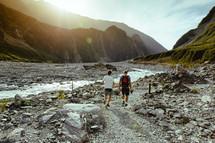 Men walking near a river through the mountains.