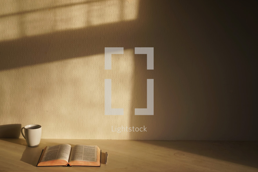 coffee mug, Bible, and pen in an empty room