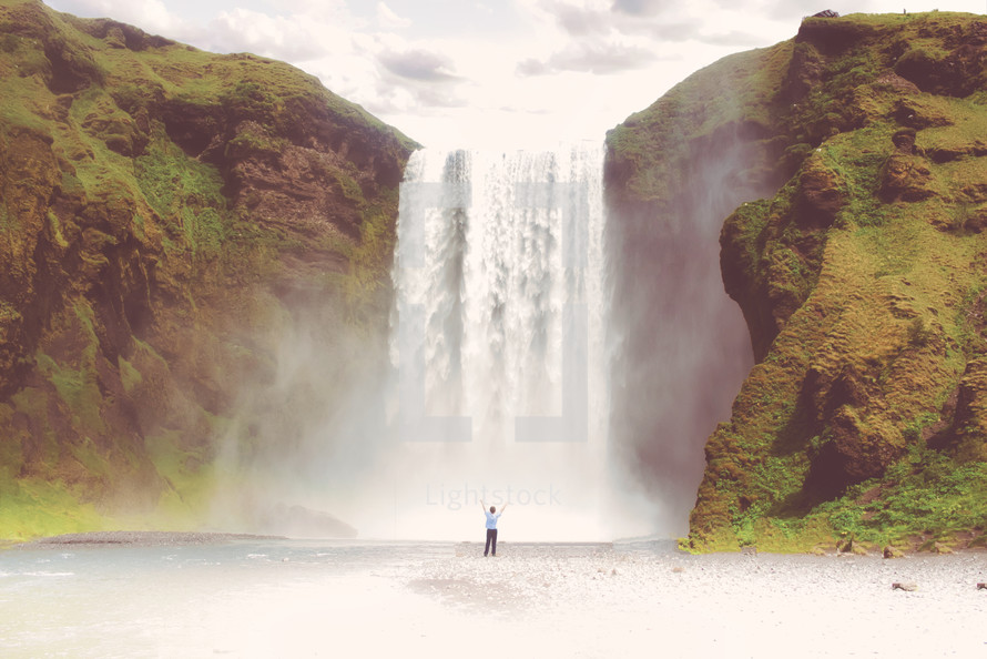 person with hands raised standing in front of a waterfall