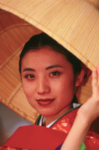 Japanese woman in kimono under a straw hat