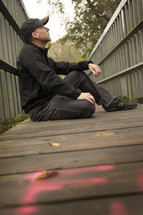 a man sitting on a boardwalk thinking and looking up at the sky