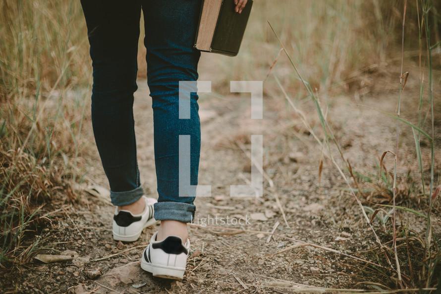 girl walking carrying a Bible