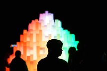 silhouettes in front of a glowing rainbow sculpture