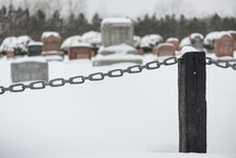 chain on a fence and graveyard in snow